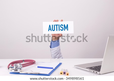 Doctor Holding Placard written AUTISM