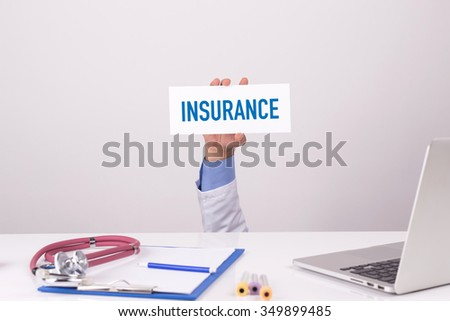 Doctor Holding Placard written INSURANCE