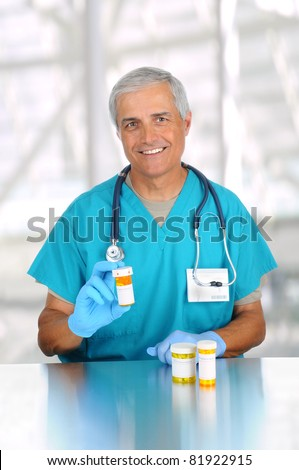 Doctor holding prescription medicine bottle in modern medical facility. Man is wearing scrubs and stethoscope. Vertical format. - stock photo
