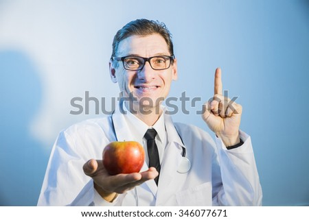 doctor holding red Apple and smiling