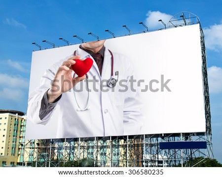 doctor holding red heart shape on billboard with white space  - stock photo