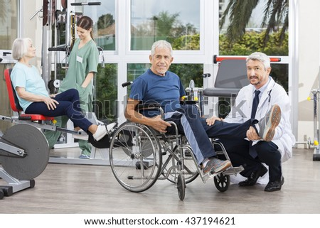 Doctor Holding Senior Man's Leg In Wheelchair At Fitness Center - stock photo