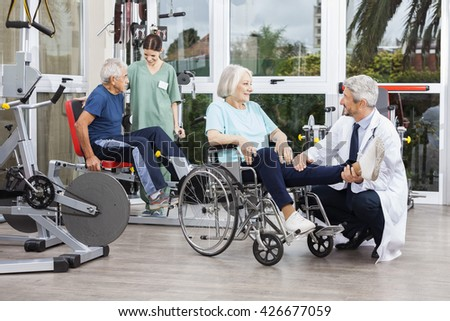 Doctor Holding Senior Woman's Leg In Wheelchair At Fitness Cente - stock photo