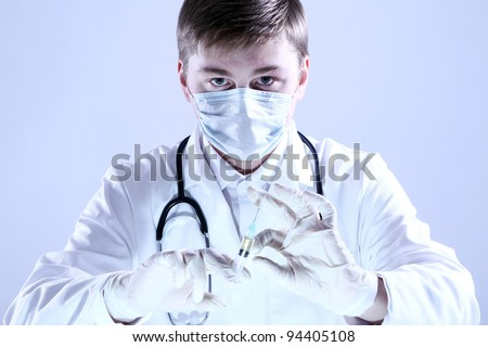 Doctor holding syringe in hand - stock photo