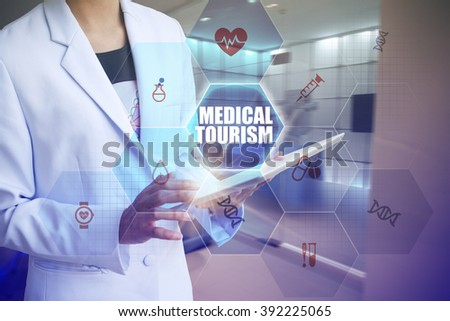 Doctor holding tablet with MEDICAL TOURISM text and working with modern computer interface , E-Health concept , business concept , business idea - stock photo