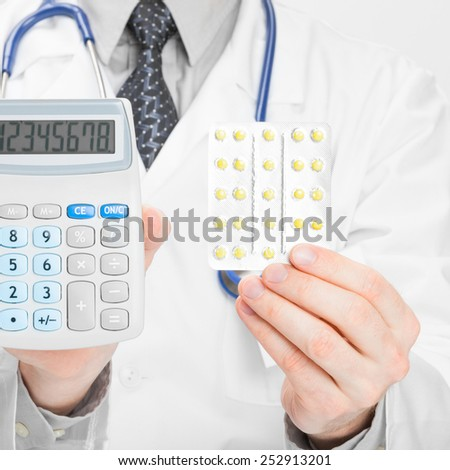 Doctor holdling calculator and pills in hands - studio shot - stock photo