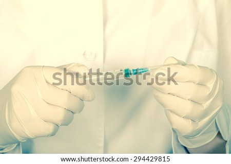 Doctor holds in hands a syringe with a needle closed. Close-up. In the hands wearing surgical gloves. Tinted. - stock photo