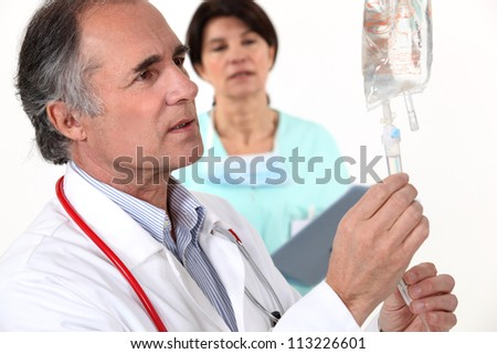 Doctor hooking up an IV - stock photo