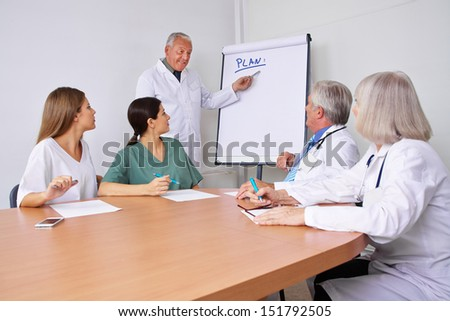 Doctor in a team presentation explaining his plan on a flipchart - stock photo