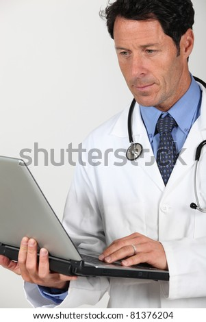 Doctor in a white coat and stethoscope with a laptop computer - stock photo