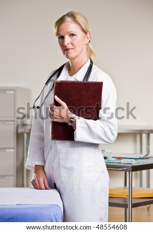 Doctor in doctor office holding notebook - stock photo