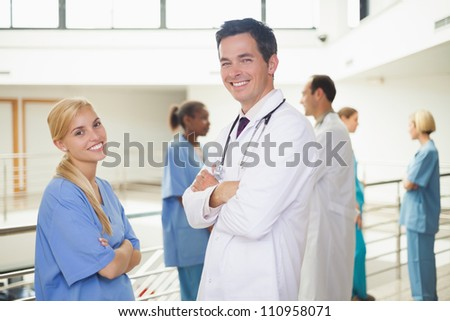 Doctor in front of a nurse with arms crossed in hospital corridor - stock photo