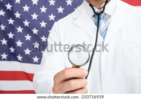 Doctor In Front Of American Flag Holding Stethoscope - stock photo
