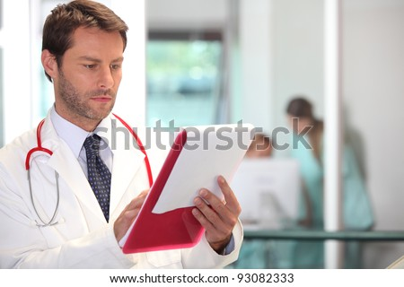 doctor in hospital reading charts - stock photo