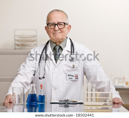 Doctor in lab coat and stethoscope in science laboratory doing research with test tubes and beakers