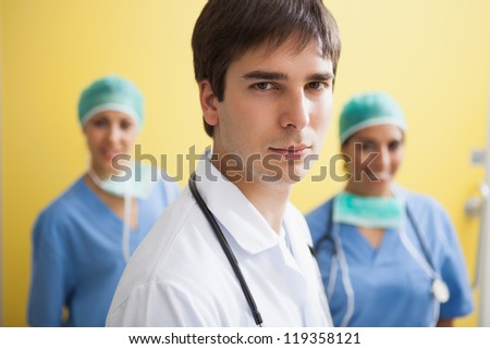 Doctor in labcoat with two smiling nurses in scrubs in background