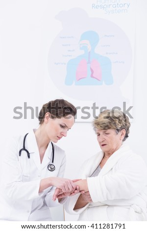 Doctor in medical uniform examining patient's hand, sitting in light hospital office