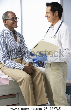 Doctor In Surgery With Male Patient Reading Notes - stock photo