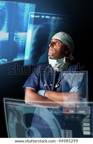 Doctor in uniform with X-rays and digital  screens and keyboard - stock photo