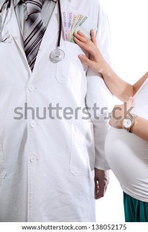 Doctor in white coat is offered money from pregnant woman - stock photo