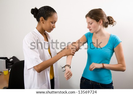 Doctor inspecting the arm of her patient - stock photo
