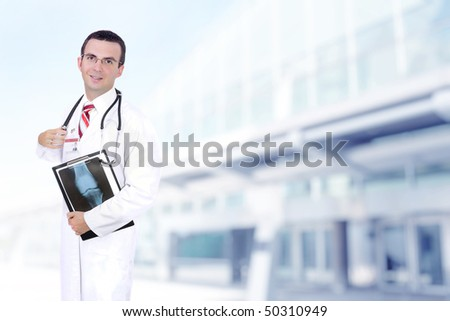 Doctor (intern) stand near the Hospital main Entrance with x-ray image. - stock photo