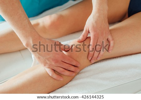Doctor is examing his patient knee. Close up