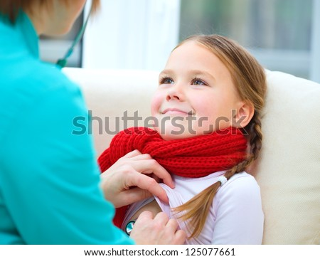 Doctor is examining a little girl using stethoscope, indoor shoot - stock photo