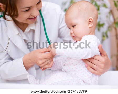 Doctor is examining cute little child - stock photo