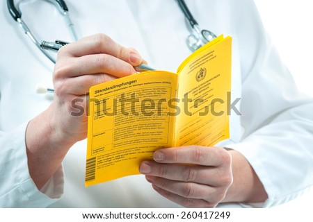 Doctor is filling out an international certificate of the vaccination - stock photo