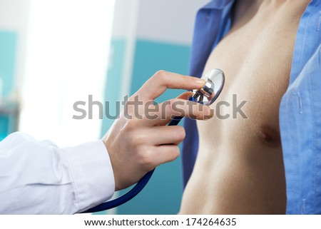 Doctor is listening to the heart of the patient - stock photo