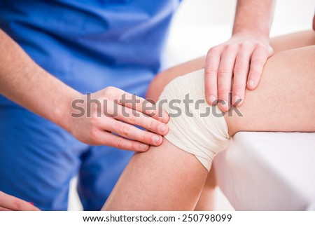 Doctor is rewinding knee bandage to young woman.