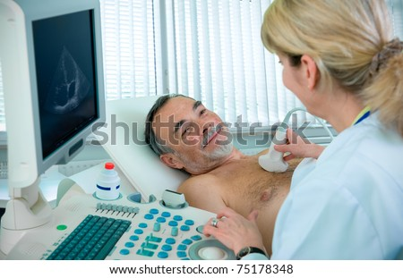 Doctor is using ultrasound machine to scan the heart of a senior male patient - stock photo