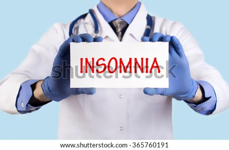 Doctor keeps a card with the name of the diagnosis -?? insomnia. Selective focus. Medical concept. - stock photo