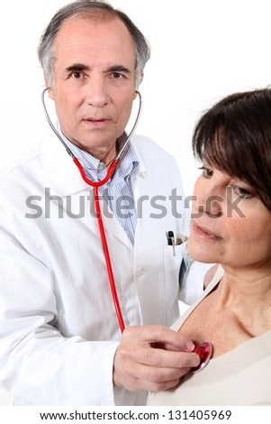 Doctor listening to a woman's chest - stock photo
