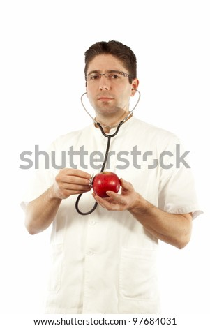 Doctor listening to an apple using stethoscope - stock photo