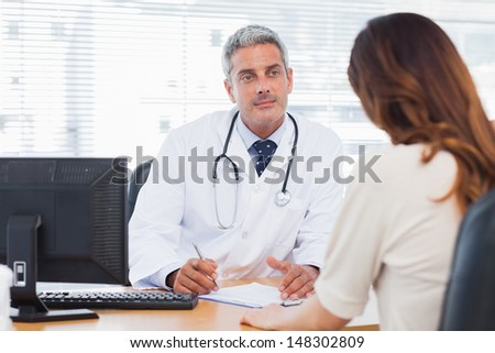 Doctor listening to his patient talking about her illness in medical office - stock photo