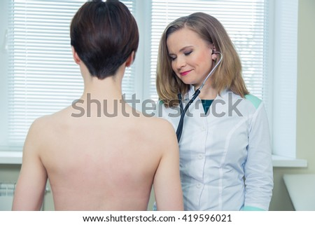 Doctor listening to patients chest with stethoscope in his office at the hospital - stock photo