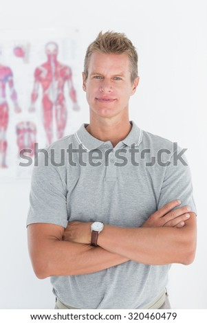 Doctor looking at camera with arms crossed in medical office - stock photo