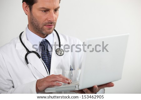Doctor looking at  laptop - stock photo