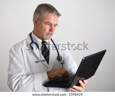 Doctor looking down at laptop computer screen - stock photo