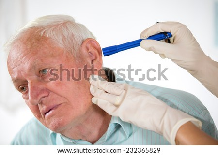 Doctor looking into patient's ear, selective focus - stock photo