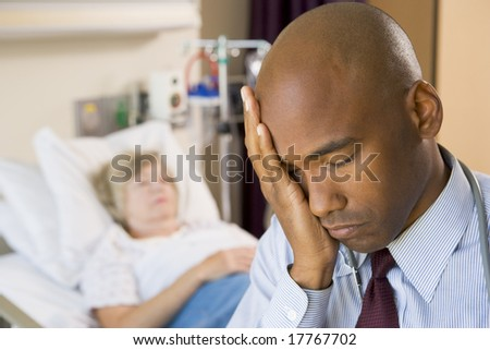 Doctor Looking Tired And Frustrated In Hospital Room - stock photo