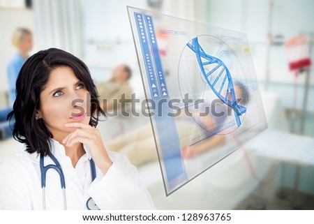Doctor looking up at screen showing blue DNA helix data