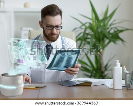 Doctor looking x-ray of his patient at his office. Using futuristic virtual computer interface