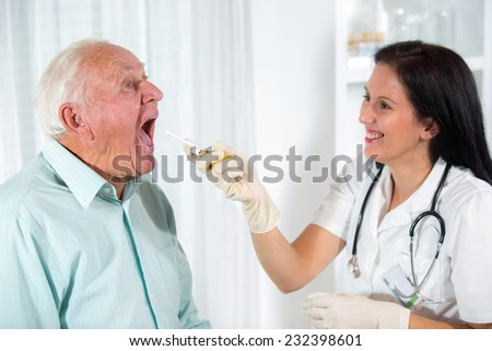 Doctor looks in the throat an older man - stock photo