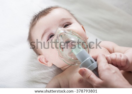 Doctor makes inhalation to a sick little baby. Health care and medicine concept at pediatrician department.