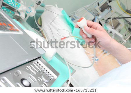 doctor makes ultrasound study in hospital ward. - stock photo