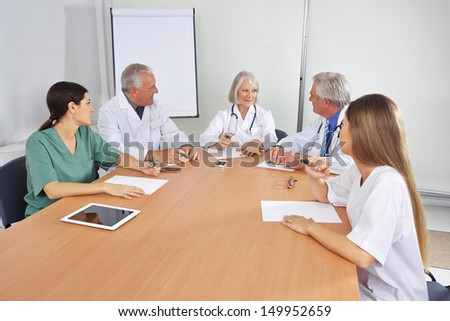 Doctor making work schedule in team meeting with colleagues - stock photo