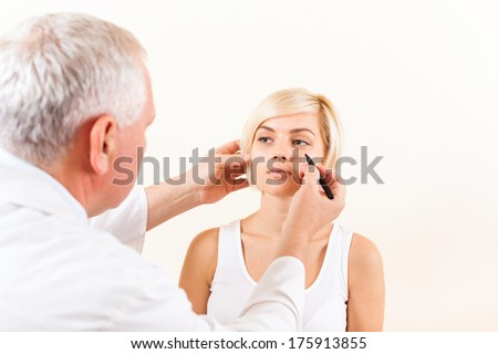 doctor male plastic surgeon with patient examine woman, draw on face - stock photo